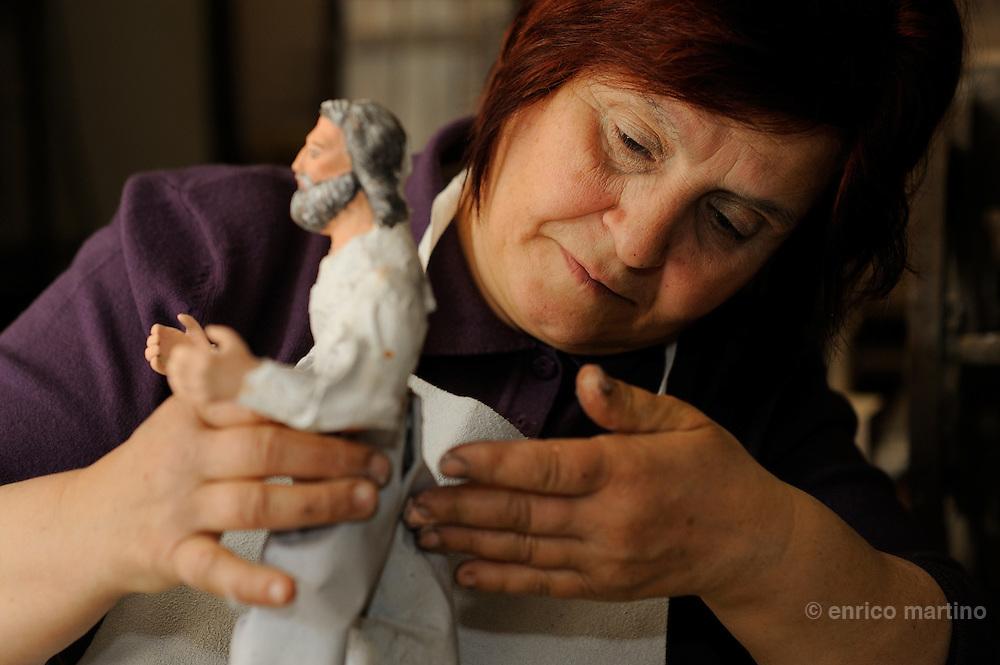 Martano, near Lecce. Maddalena, the wife of tha craftman Luigiu Baldari is specialided to dress the papier-mâché statues.