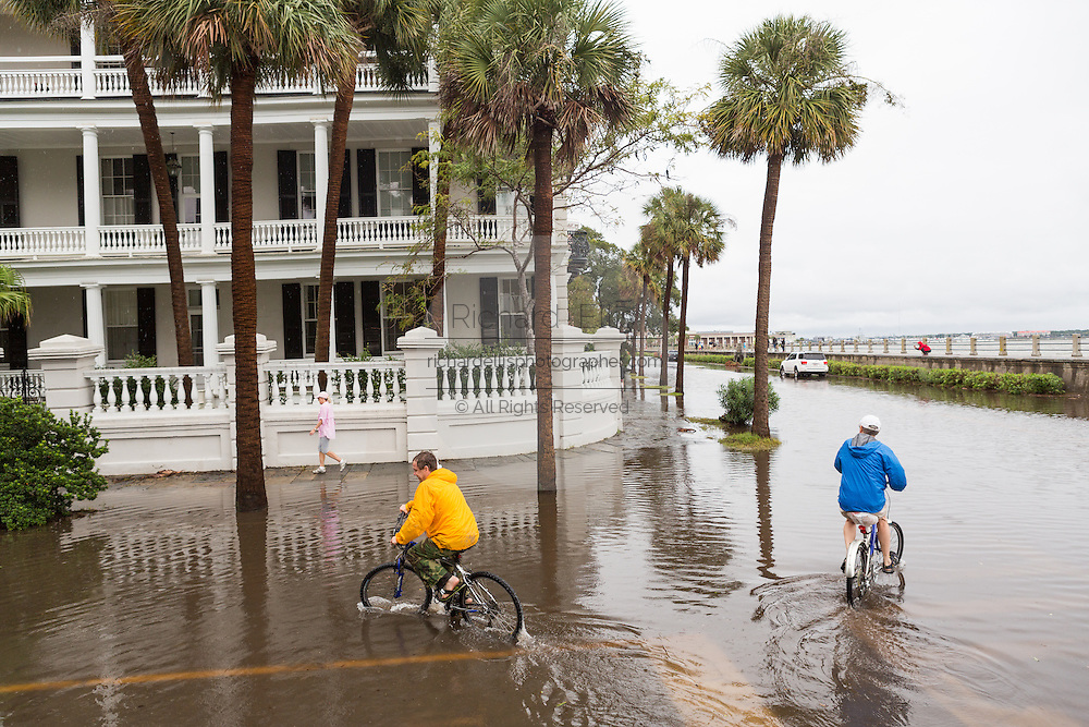 Bicyclists ride through floodwater along the Battery in the historic district as Hurricane Joaquin brings heavy rain, flooding and strong winds as it passes offshore October 4, 2015 in Charleston, South Carolina.