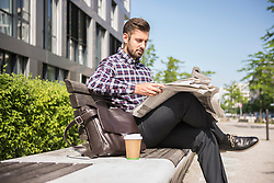 Young man sitting on bench and reading newspaper, Munich, Bavaria, Germany