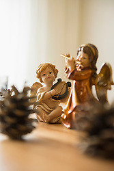 Decorative Christmas angel figurines with musical instruments and pine cone on the table, Bavaria, Germany