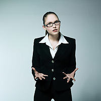 studio shot portrait of a beautiful young angry woman in a costume suit