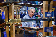 16 MAY 2009 -- PHOENIX, AZ: People look at a replica of a Colt 1888 Lightning slide action rifle in the Stoeger booth at the NRA convention in Phoenix, AZ, Saturday. About 60,000 people were expected to attend the trade show at the 138th annual National Rifle Association Annual Meeting in the Phoenix Convention Center in Phoenix, AZ. Photo by Jack Kurtz