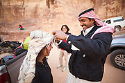 A Bedouin man helps a female tourist put on the traditional Arab keffiyeh headress in Wadi Rum, Jordan.