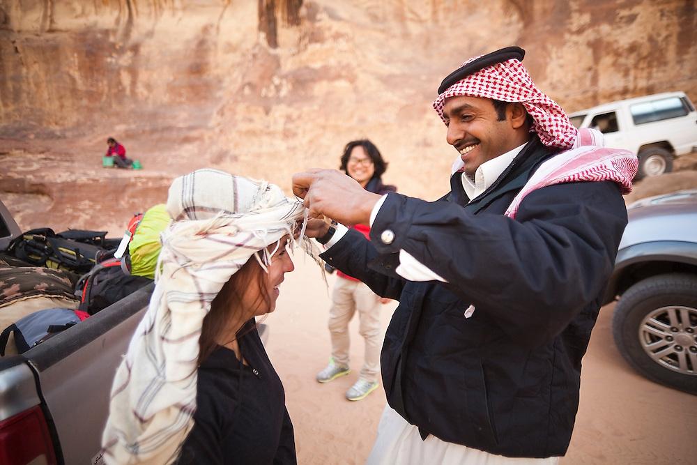 A Bedouin man helps a female tourist put on the traditional Arab keffiyeh headress in Wadi Rum, Jordan.