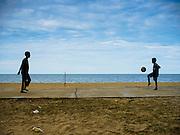 15 JUNE 2105 - BAN THONG, NARATHIWAT, THAILAND:   Boys kick a soccer ball on a basketball court at Ban Thong beach in Narathiwat, Thailand.      PHOTO BY JACK KURTZ