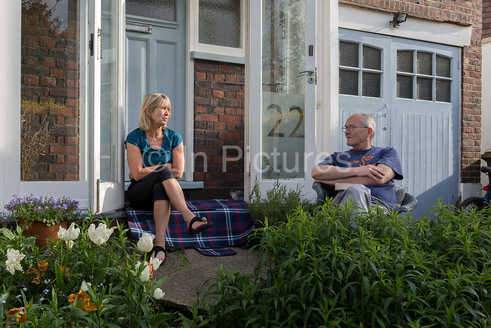 As the country continues the UK governments Coronavirus lockdown with social distancing rules still in effect, a middle-class couple sit on the porch in the front garden outside their home in Herne Hill, south London, on 17th May 2020, in London, England.
