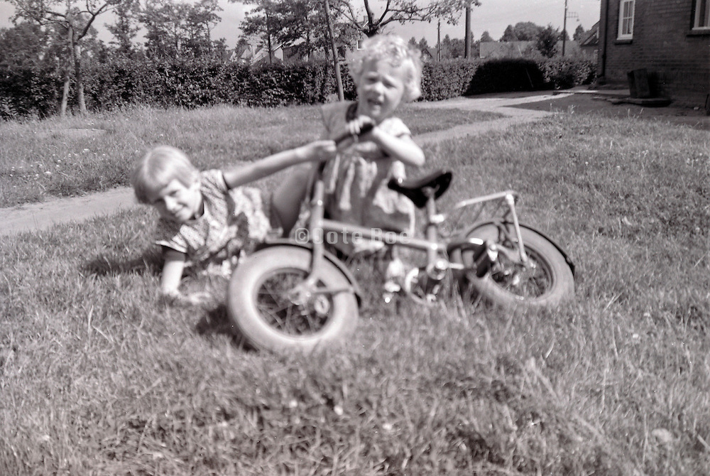 sisters playing with bicycle 1960s