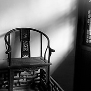 An antique chair sits in the window light. China.