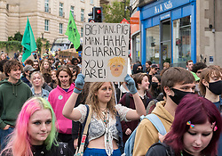 © Licensed to London News Pictures; 22/10/2021; Bristol, UK. A young woman carries a placard featuring the UK Prime Minister Boris Johnson during a pre-COP26 Bristol Youth Strike 4 Climate protest takes place in the city centre. Students and staff from Bristol and Bath universities, colleges, and schools to protest inaction of governments globally, and about the lack of progress by Bristol City Council in tackling the climate and ecological crisis, on issues of clean air, Bristol airport expansion and climate justice. Photo credit: Simon Chapman/LNP.