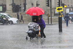 © Licensed to London News Pictures. 27/09/2019. London, UK. A couple are seen with a pram during heavy downpour in London. According to the Met Office, this weekend is set to be washout with over 2o hours of rainfall in the capital. Photo credit: Dinendra Haria/LNP. Photo credit: Dinendra Haria/LNP
