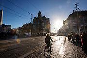 Fietsers in Amsterdam rijden over de Dam.<br /> <br /> Cyclists ride at the Dam in Amsterdam.