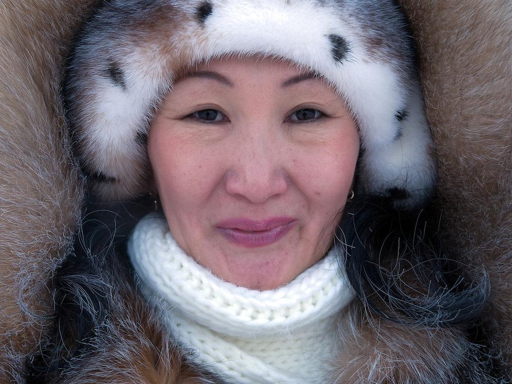 Jakutische Frau mit Kopfbedeckung geschützt gegen die extreme Kaelte in der Innenstadt von Jakutsk. Jakutsk wurde 1632 gegruendet und feierte 2007 sein 375 jaehriges Bestehen. Jakutsk ist im Winter eine der kaeltesten Grossstaedte weltweit mit durchschnittlichen Winter Temperaturen von -40.9 Grad Celsius. Die Stadt ist nicht weit entfernt von Oimjakon, dem Kaeltepol der bewohnten Gebiete der Erde.<br /> <br /> Yakut women protected with headgears against the extrem climate  in the city center of Yakutsk. Yakutsk was founded in 1632 and celebrated 2007 the 375th anniversary - billboard announcing the celebration. Yakutsk is a city in the Russian Far East, located about 4 degrees (450 km) below the Arctic Circle. It is the capital of the Sakha (Yakutia) Republic (formerly the Yakut Autonomous Soviet Socialist Republic), Russia and a major port on the Lena River. Yakutsk is one of the coldest cities on earth, with winter temperatures averaging -40.9 degrees Celsius.