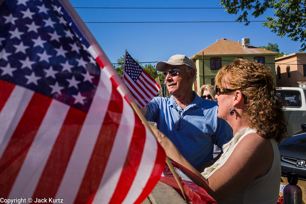 30 JUNE 2012 - PRESCOTT, AZ: A couple puts patriotic bunting on a float at the Prescott Frontier Days Rodeo Parade. The parade is marking its 125th year. It is one of the largest 4th of July Parades in Arizona. Prescott, about 100 miles north of Phoenix, was the first territorial capital of Arizona.    PHOTO BY JACK KURTZ