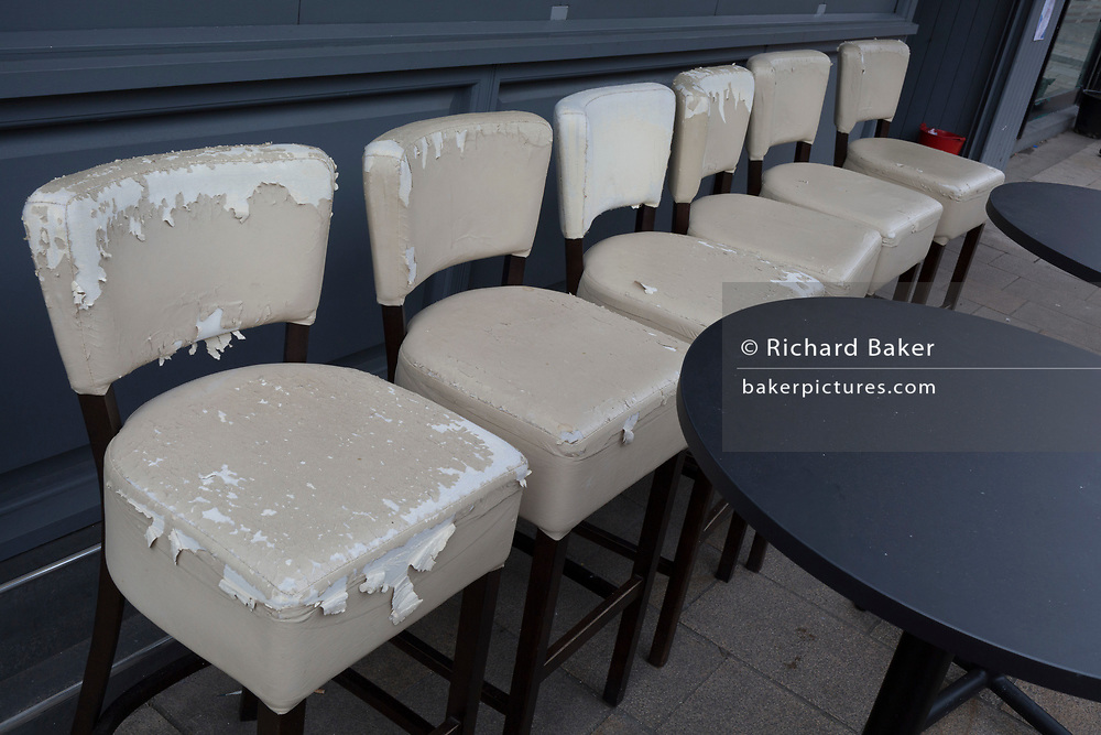 Peeling seats lined-up in front of seating outside a bar in Bromley town centre, on 3rd February 2020, in London, England