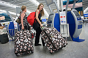"A slightly comical scene of modern air travel as two lady passengers haul matching suitcases at the British Airways self-check-in kiosk at Heathrow Airport's Terminal 5. The self-service kiosks that have been developed to allow customers to process their own ticketing on arrival at this aviation hub for British Airways. Once they've chosen their seat and printed a boarding pass, they can go straight to the Fast Bag Drop desk at the airport. There, baggage will be tagged by an agent and sent to the aircraft. At a cost of £4.3 billion, Terminal 5 has the capacity to serve around 30 million passengers a year. From writer Alain de Botton's book project ""A Week at the Airport: A Heathrow Diary"" (2009)."
