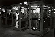 Telephone booth with homeless youths Amsterdam Central Station