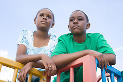 Bother and sister; on a climbing frame; looking sad,