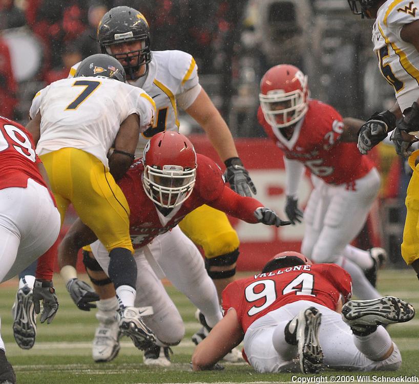 Dec 5, 2009; Piscataway, NJ, USA; Rutgers linebacker Steve Beauharnais (42) upends West Virginia running back Noel Devine (7) during first half NCAA Big East college football action between Rutgers and West Virginia at Rutgers Stadium.