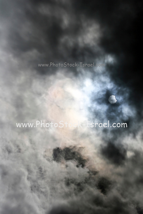 Partial solar eclipse seen through low clouds. This is the solar eclipse of 20th March 2015. This was a total eclipse, but totality was only visible in a small path across the North Atlantic. It was visible as a partial eclipse across Europe and North Africa. 20th March 2015 also saw the spring equinox. Photographed in Israel