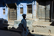 Indian man walking past ancient doorways in the village of Narlai in Rajasthan, Northern India<br /> FINE ART PHOTOGRAPHY by Tim Graham