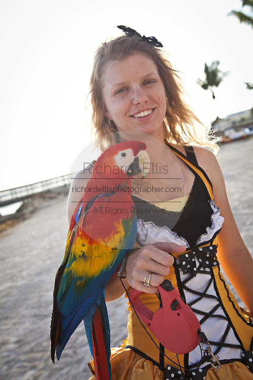 A with her macaw parrot along the beach in Key West, Florida