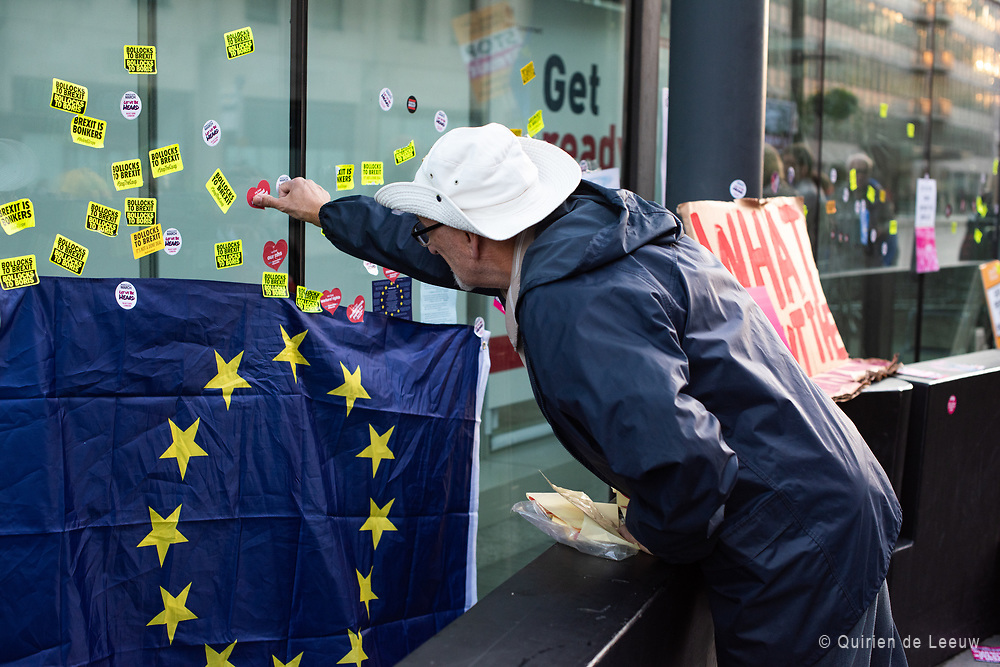 A demonstrator is putting a sticker on the window of a shop in central london