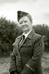 A Female re-enactor portraying Wehrmacht Heferinnen with the German Army in walking out uniform with white dress uniform blouse. She is wearing the War Merit Cross ribbon, above it pinned to her tie is the Blitz pin or brooch and on the right sleeve is the Blitz badge worn by women trained in Army communications procedures. The brooch combined with the Yellow piping (waffenfarbe) on her hat would indicate they are a Nachrichtenhelferin Wehrmacht (Signals Assistants with the German Army). Heferinnen were the German Armed Forces female Auxiliaries who worked with the German Army in World war two in much the same way the British Auxiliary Territorial Service (ATS) did with the British Army of WW2. <br /> At various periods of time during the second world war Helferinen were sometimes classified as military personnel other times as uniformed civilians employed by the German Armed Forces (Wehrmacht).<br /> <br />  17 July 2016<br />  Copyright Paul David Drabble<br />  www.pauldaviddrabble.photoshelter.com