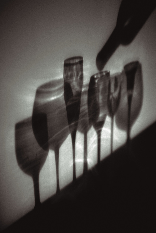 wine glass shadows with bottle pouring,black and white,verticle