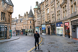 Edinburgh, Scotland, UK. 26 December 2020. Scenes from Edinburgh City Centre on a wet and windy Boxing Day during storm Bella. Today is first day that Scotland is under level 4 lockdown and all non essential shops and businesses are closed. As a result the streets are almost deserted with very few people venturing outside.  Pic ; Historic Cockburn Street has a solitary jogger. Iain Masterton/Alamy Live News