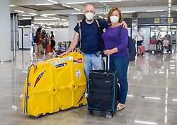 © Licensed to London News Pictures.  30/06/2021. Palma de Mallorca, Spain. Dr Audrius and Mrs Rasa Simaitiene from London arrive at Palma Airport in Mallorca as Balearic Islands are on the UK 'green list' from 4am, today. Photo credit: Marcin Nowak/LNP