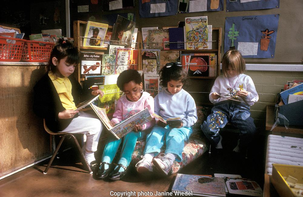 Children quietly reading in book corner of  London primary school.