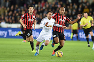 Leon Britton of Swansea city ©  is tackled by Karl Henry  of QPR (r) .Barclays Premier league match, Swansea city v Queens Park Rangers at the Liberty stadium in Swansea, South Wales on Tuesday 2nd December 2014<br /> pic by Andrew Orchard, Andrew Orchard sports photography.