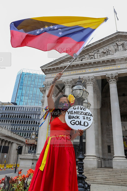 A woman waving a Venezuelan flag holds a placard calling the Bank of England to release Venezuela's gold in Central London on Saturday, Aug 15, 2020, to protest against the Bank of England's decision to hold the Venezuelan gold. <br /> The bars are among the 400,000 bars of gold held in the Bank's vaults, but there is a political dispute about their rightful owner. <br /> The Bank of England is blocking the release of 31 tonnes of gold valued at nearly $1bn(£805m) and intended to combat the coronavirus in Venezuela. (VXP Photo/ Vudi Xhymshiti)
