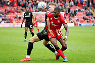 Walsall FC forward Corey Blackett-Taylor (38) and Barnsley forward Cauley Woodrow tussle for the ball during the EFL Sky Bet League 1 match between Walsall and Barnsley at the Banks's Stadium, Walsall, England on 23 March 2019.