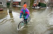 Nederland,  nabij Bergen (Limburg), 5 jan 2003.Hoog water in de Maas zorgt voor overlast door overstromingen. .Voor kinderen kan het ook leuk zijn: met je fietsje door het hoge water crossen..Wateroverlast. .Foto (c) Michiel Wijnbergh/Hollandse Hoogte