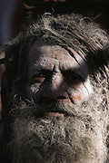 Portrait of a naga who is covered in ash at Kumbh Mela.  Every 12 years, millions of devout Hindus celebrate the month-long festival of Kumbh Mela by bathing in the holy waters of the Ganges at Hardiwar, India. Hundreds of ashrams set up dusty, sprawling camps that stretch for miles. Under the watchful eye of police and lifeguards, the faithful throng to bathe in the river.
