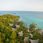 Six of seven bungalows and coral rag forest viewed from the historic 1904 lighthouse at sunrise, with the Indian Ocean in the background. Chumbe Island Coral Park, Zanzibar, Tanzania is an internationally-awarded eco-resort and the first private, not-for-profit marine preserve in the world.