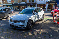 A parked car shows damage to its left front corner as workers clear up the debris following a high speed crash involving two high performance cars on Chiselhurst High Street in South East London. London, August 22 2019.