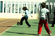 Children playing soccer in a school yard