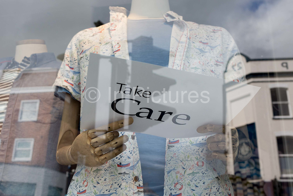 At the beginning of the second week of the UKs Coronavirus lockdown and in accordance with government guidelines for social distancing and the forced closure of all shops and local businesses, the wooden fingers of a mannequin holds a sign saying Take Care, in the window of a clothing shop in East Dulwich, on 30th March 2020, in London.