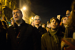 """Fathers are praying next to Notre Dame Cathedral with a statue of Virgin Mary during an evening of prayer and songs organized by Catholics community the day after Notre Dame Cathedral blaze with a march organized from Saint-Sulpice church to Saint Michel and finally next to Notre Dame Cathedral in Paris early on April 16 the day after the beginning of the fire , 2019. A huge fire that devastated Notre-Dame Cathedral is """"under control"""", the Paris fire brigade said early on April 16 after firefighters spent hours battling the flames. Photo by Raphael Lafargue/ABACAPRESS.COM"""