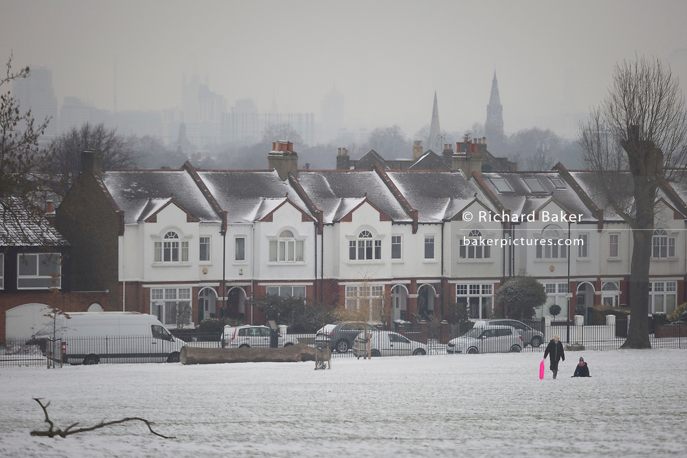 An adult pulls a child uphill on a small sledge in Ruskin Park, south London during the bad weather covering every part of the UK and known as the 'Beast from the East' because Siberian winds and very low temperatures have blown across western Europe from Russia, on 1st March 2018, in Lambeth, London, England