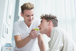 Young man feeding grapes to another man, smiling