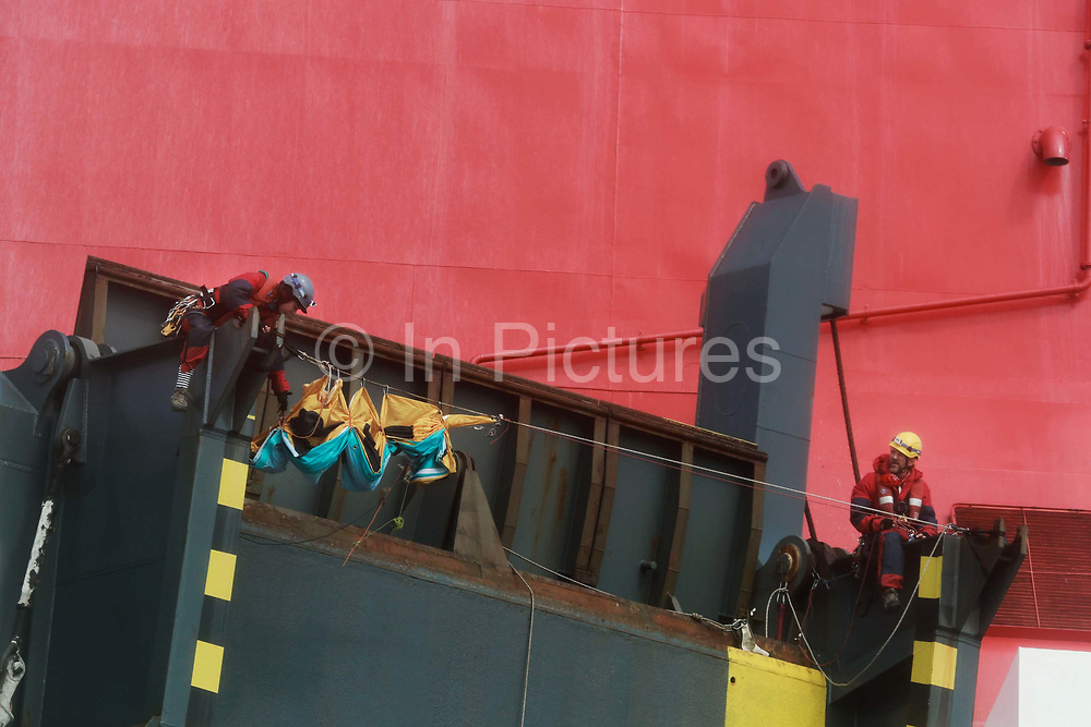 Two Greenpeace climbers scale the back of the cargo ship to prepare to deploy a banner calling for VW to ditch diesel.September 21st 2017, Thames Estuary, Kent, United Kingdom. Greenpeace volunteers in kayaks, speed boats and climbers on the jetty prevent the 23,498-tonne cargo ship Elbe Highway from docking at Sheerness in Kent.  The cargo ship is bringing Volkswagen diesel cars into the UK and the Greenpeace action is to prevent this from happening and to make VW ditch diesel. Two climbers board the ship and hang a banner on the roll-on roll-off part of the ship preventing any cars from being off-loaded. The action is part of a long running Greenpeace campaign to curb diesel emmissions and air pollution broght on by diesel cars.