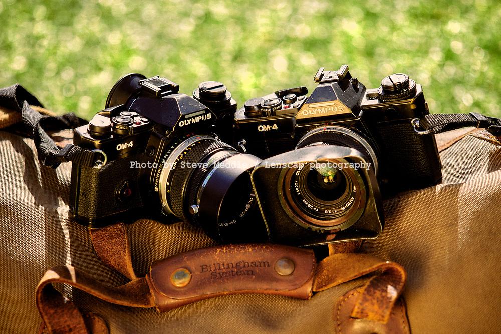 London, England - February 26, 2021: Two Olympus 35mm film single lens reflex cameras sitting on a Billingham 550 camera bag