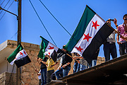 Men waving a Syrian Revolutionary Flag, which consists of three colours: red, white and black, with three red stars of five angles each against the one with two green stars, attend a public gathering on Friday, Jun 29, 2012 - to protest against the suppressive measures of President Bashar Al-Assad who forced them to arm and fight for their freedom. (Photo by Vudi Xhymshiti)