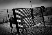 Some of the migrants are climbing the fence into the square where they two time a day are getting free food. The rain is pouring down and the boys want to get under cover.