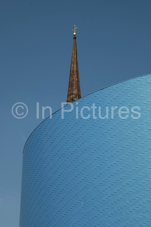 Blue architectural exterior of the Wave with Christchurch Spire in the UK City of Culture 2021 on 23rd June 2021 in Coventry, United Kingdom. The UK City of Culture is a designation given to a city in the United Kingdom for a period of one year. The aim of the initiative, which is administered by the Department for Digital, Culture, Media and Sport. Coventry is a city which is under a large scale and current regeneration. The Wave is an indoor water park which holds the record for the largest wave pool in the UK, at a capacity of 20 million litres.