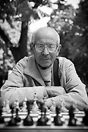 A senior man sits at a chess table in Kiev's Shevchenko Park, waiting for someone -- a passing friend or stranger, it doesn't matter -- to play against him. The chess board is reflected in his eyeglasses.
