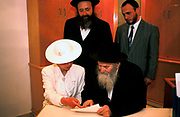 A Rabbi helps the Bride to sign the Wedding record at a wedding in Jerusalem, Israel